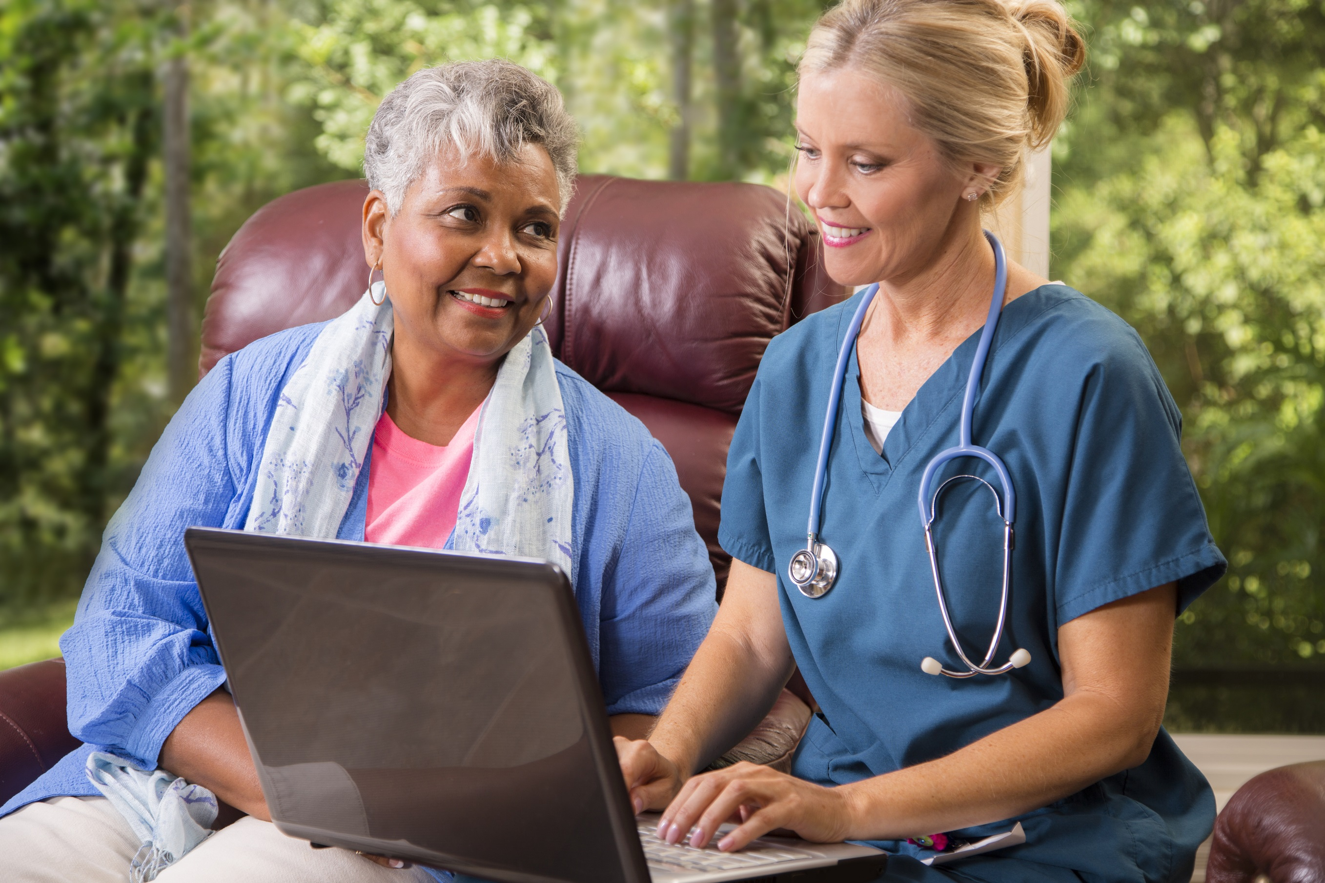Caring home healthcare nurse conducts medical consultation with African descent senior adult woman at her home or nursing home. The female patient is sitting in her comfortable chair while reviewing her medical information on a laptop with her nurse or doctor.