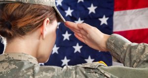 a female soldier salutes an American flag.